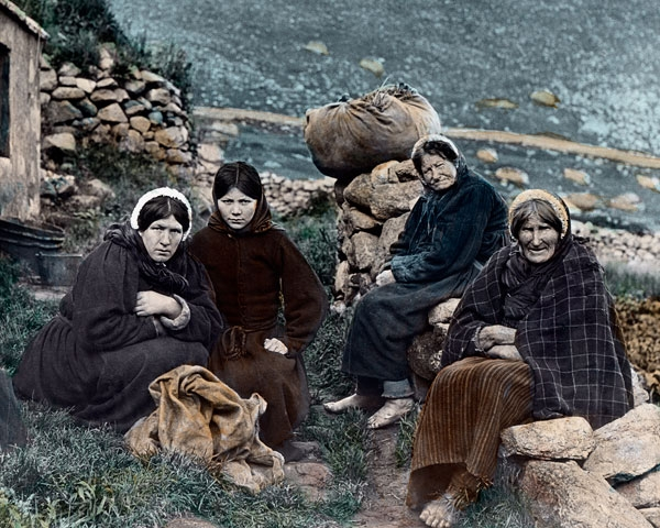 Hand tinted photo of island women.  Notice that none have shoes.  The one on the far right has straw tied round her legs for warmth, and the one next to her has a pair of trousers or long johns under her skirt.  You can see the very bottom of both under the hem of the skirts.