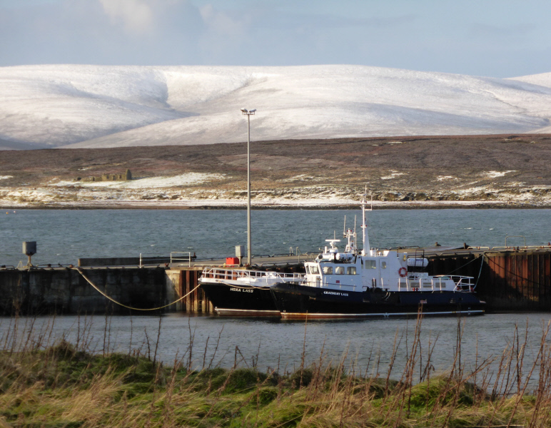 Sutherland Pier, looking across the island of Fara to the snow-covered hills of Hoy.